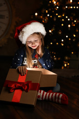 Cute child opening magic gift box near Christmas tree at night