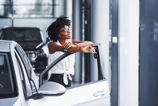 Young african american woman in glasses stands in the car salon near vehicle with keys in hands