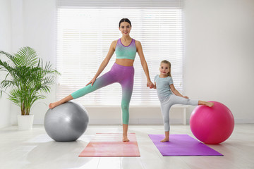 Woman and daughter doing exercise with fitness balls at home