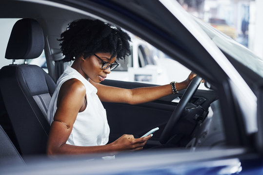 Using phone. Young african american woman sits inside of new modern car