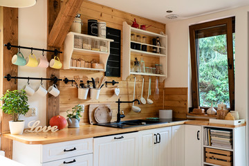 Interior of cozy wooden kitchen with window in a cottage in the country.  Vintage kitchenware and...