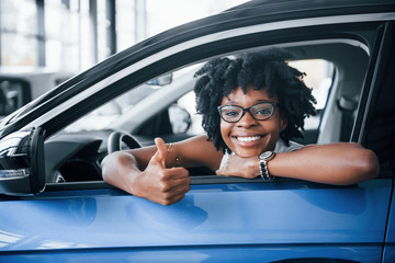Shows thumb up. Young african american woman sits inside of new modern car
