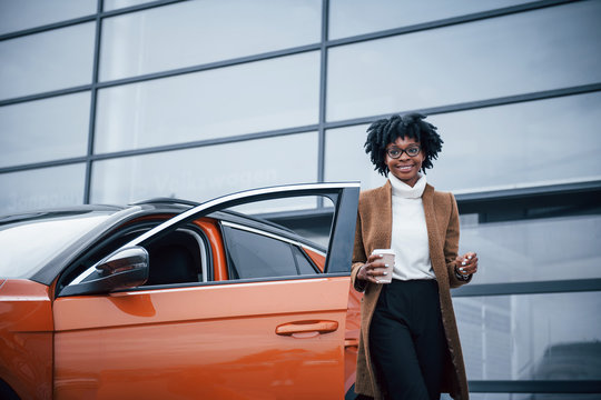 With cup of drink. Young african american woman in glasses stands outdoors near modern car