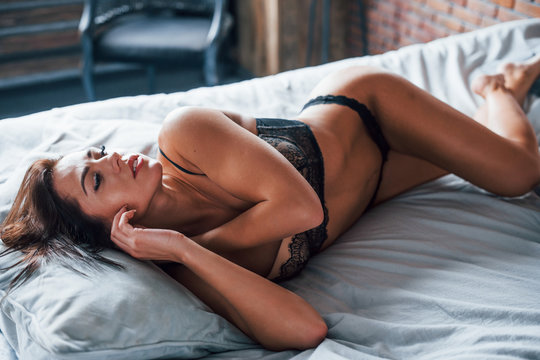 Beautiful sexy brunette woman lying down on the bed at morning time