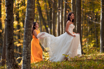 Bride and bridesmaid in the forest