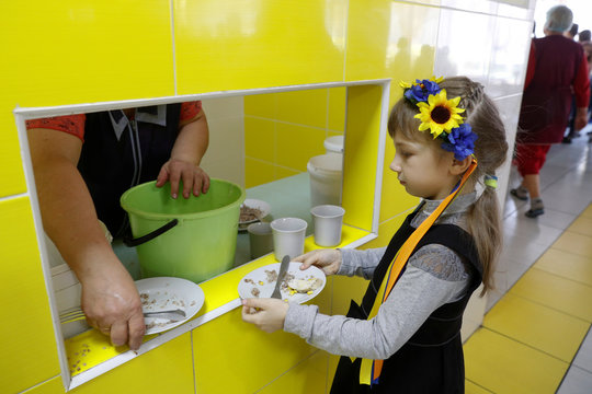 Schoolgirl leaves a plate with remains of food after lunch at a school canteen in Kiev