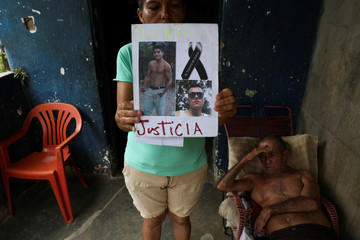 Judith Cortez holds pictures of her sons Jose Alfredo and Anderson Torres as her husband Romulo rests at their home, in El Tocuyo