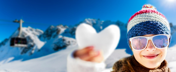 Wall Mural - I love winter. Portrait of happy young girl holding in hand snow heart in winter time, ski slope in the background. Verbier, Switzerland, Alps.