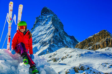 Portrait of happy young girl in the snow, ski slope and Matterhorn in the background.