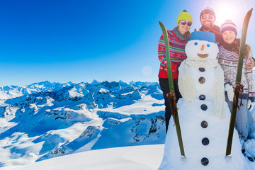 Wall Mural - Happy family enjoying winter with snowman vacations in mountains, Playing with snow and sun in high mountains. Winter holidays.