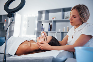 Woman lying down in spa salon and have face cleaning procedure by professional cosmetologist