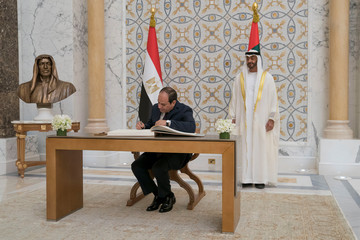 Abu Dhabi's Crown Prince Sheikh Mohammed bin Zayed al-Nahyan stands as Egyptian President Abdel Fattah al-Sisi signs the guest book in Abu Dhabi