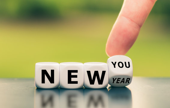 "Hand turns a dice and changes the expression ""new year"" to ""new you""."