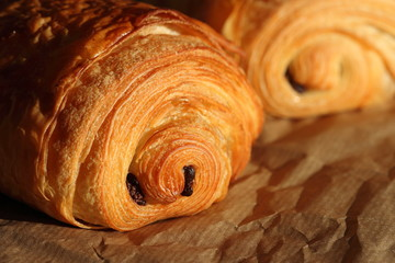 Freshly backed french pastry - petit pain au chocolat shiny in the rays of the morning sun