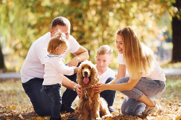 Cheerful young family with dog have a rest in an autumn park together