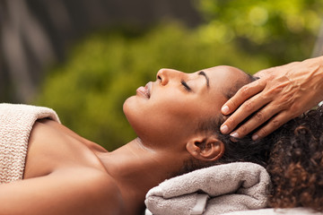 Beautiful african woman relaxing with face massage