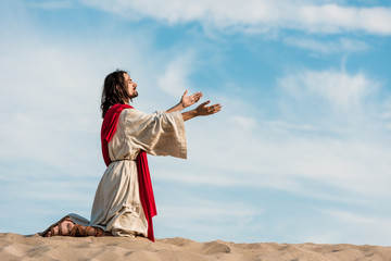 jesus praying on knees on sand in desert against sky Fotomurales