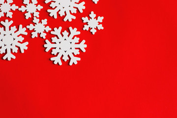 Wooden white snowflakes on red background.