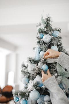 woman decorating beautiful Christmas tree