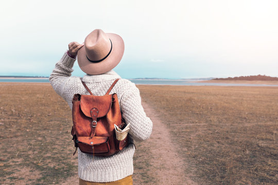 young man traveling through nature with backpack and hat