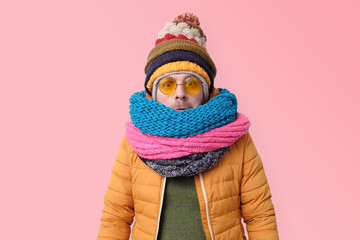 Handsome caucasian funny man in several hats and scarfs.