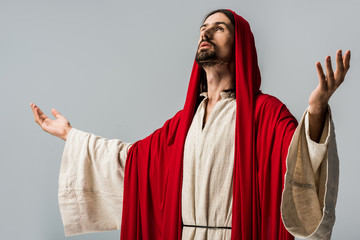 bearded man in red hood praying with outstretched hands isolated on grey
