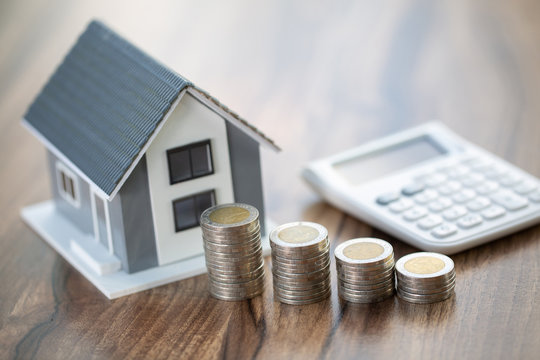 House model and coin, calculator on table for finance ,banking concept.Calculating mortgage , Saving money for buy a new house and loan for plan business investment for real estate.