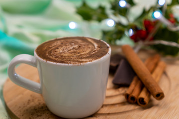 Closeup of a cup of flat white coffee next to cinnamon sticks and dark chocolate in a festive Christmas decor.