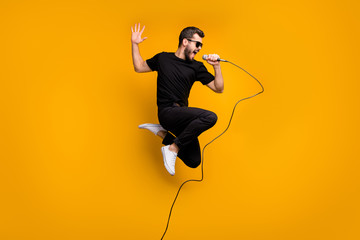 Full body profile photo of crazy hipster guy jumping high holding microphone music lover singing favorite song wear sun specs black t-shirt pants isolated yellow color background Wall mural