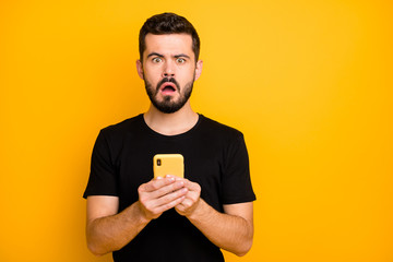 Portrait of impressed guy use his cellphone read unbelievable social network blogging information feel confused emotions stay stupor wear modern clothes isolated yellow color background