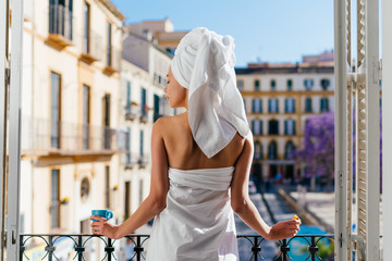 hotel guest stands on the balcony with her back to the camera, drinking tea