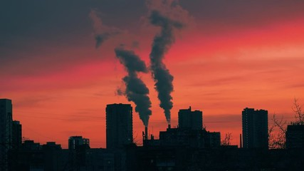 Klistermärke - Smokestacks emitting smoke in red sunset sky over dark city skyline silhouette. Timelapse, 4K UHD.
