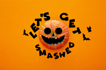 top view of pumpkin on orange background with lets get smashed illustration, Halloween concept