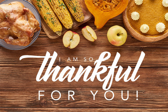 top view of pumpkin pie, turkey and vegetables served at wooden table with i am so thankful for you illustration