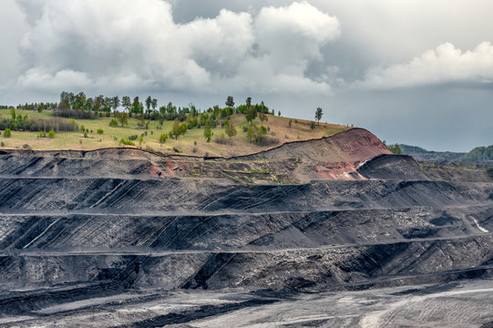 A large quarry with many horizons and ledges. Vertical bedding of coal seams.