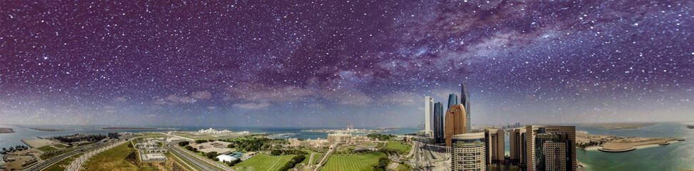 Amazing panoramic aerial view of Abu Dhabi skyscrapers from Corniche Road on a starry night with milky way