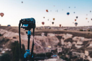 Hot air balloon flying over rock landscape at Turkey. Photo camera on a tripod in the foreground.