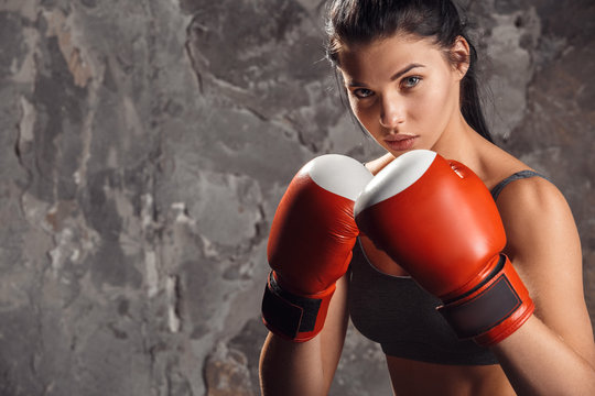 Boxing. Woman boxer in gloves standing isolated on wall ready to kick confident