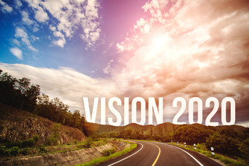 The word vision 2020 behind the tree of empty asphalt road at golden sunset and beautiful blue sky. Concept for vision year 2020.