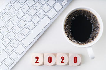 keyboard, coffee and cubes with number 2020 on white background
