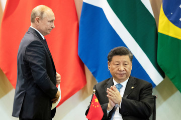 China's President Xi Jinping and Russia's President Vladimir Putin attend a meeting with members of the Business Council and management of the New Development Bank during the BRICS emerging economies at the Itamaraty palace in Brasilia