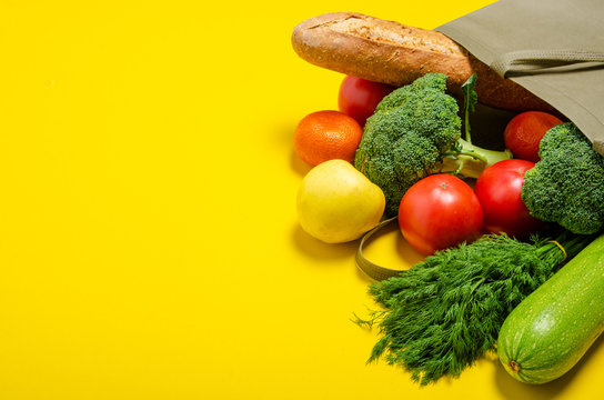 Food vegetable, bread, fruit in eco grocery bag on yellow background, top view