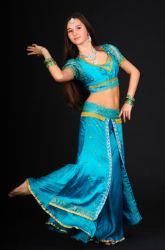 Beautiful young caucasian white woman dancing indian dances in traditional costume and posing. Isolated on dark background