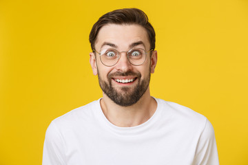 Young man looking at copyspace having a surprised or satisfied look isolated on yellow background.