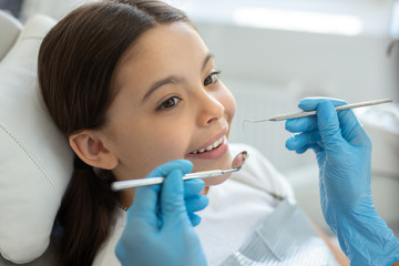 smiling client at dental procedure, dentist using dental instruments in modern dental clinic