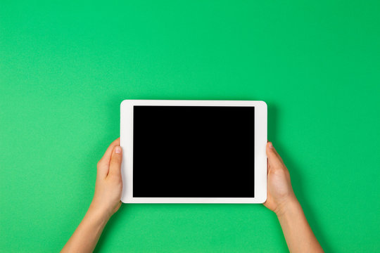 Child hands holding tablet computer on light green background
