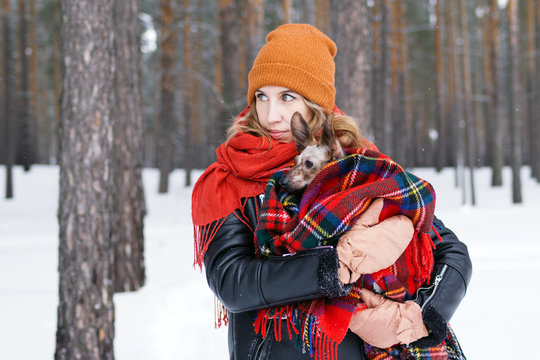 Beautiful woman is holding in hands her little dog wrapped in red checkered plaid on a walk in winter forest.