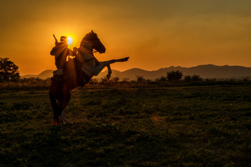 Silhouette of cowboy man riding horseback jumping at sunset and mountain background