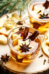 Fotobehang Thee Hot drink for New Year, Christmas or autumn holidays. Mulled cider or spiced tea or mulled white wine with lemon, apples, cinnamon, anise, cloves.