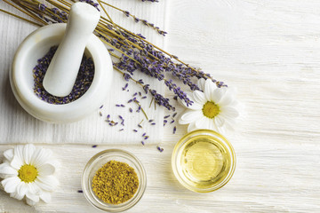 Composition with dried lavender flowers in white marble pestle and mortar and natural chamomile oil...